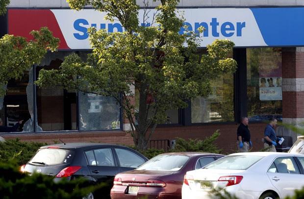 Loja de conveniências ao lado do supermercado teve vidros quebrados pelo tiroteio (Foto: Julio Cortez/AP)