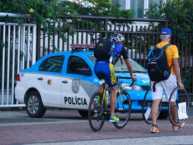 Atletas de triatlo passam junto a um carro da PM na Avenida Atlântica (Foto: Divulgação/Philippe Lima)