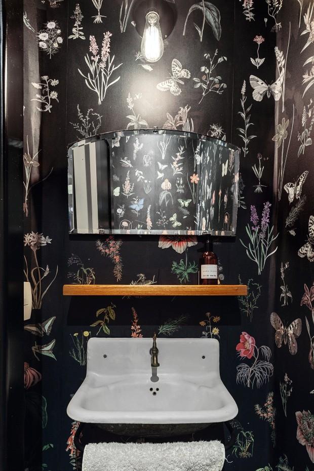 Lavabo. Papel de parede floral da Branco reveste o cômodo, com pia e espelho de antiquário (Foto: Cristiano Bauce / Divulgação)