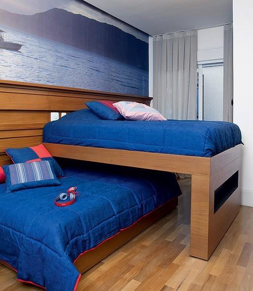 Neste quarto, projeto da arquiteta Fabiana Avanzi, as camas ficam sobrepostas na perpendicular e correm para lados opostos em rodízios no chão e embutidos em ripados de peroba na parede  (Foto: Lufe Gomes)