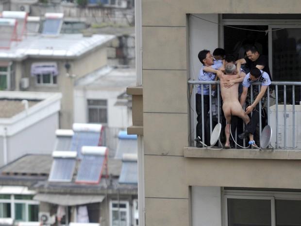 Policiais tentam agarrar e controlar um homem nu do lado de fora de uma varanda e ameaçando pular do 16º andar de um prédio em Hefei, China. O homem, cuja mãe foi encontrada morta no apartamento, acabou controlado pela polícia após um impasse de 6 horas (Foto: Reuters)