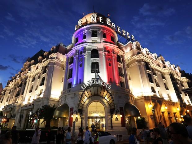 Pessoas passam pelo Palácio Negresco em Nice, na França, iluminado com as cores da bandeira francesa em homenagem às vítimas do ataque com um caminhão nesta quinta (14). Mais de 80 pessoas morreram e dezenas ficaram feridas