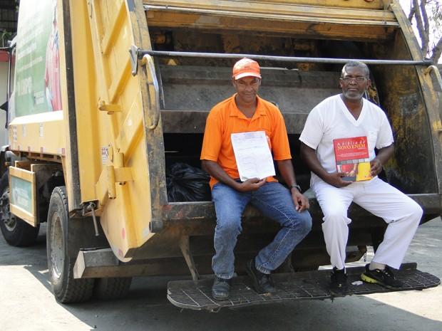 De blusa laranja, Milton Marinho exibe certificado de conclusão do Ensino Médio; de uniforme branco, Domingos Costa carrega livro de preparação para o Enem (Foto: Raquel Freitas/G1)