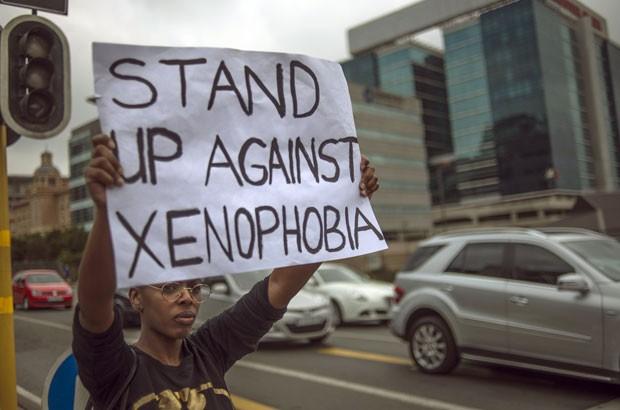 Sul-africano segura cartaz pedindo o fim da xenofobia neste sábado (18) em Johanesburgo (Foto: Mujahid Safodien/AFP)
