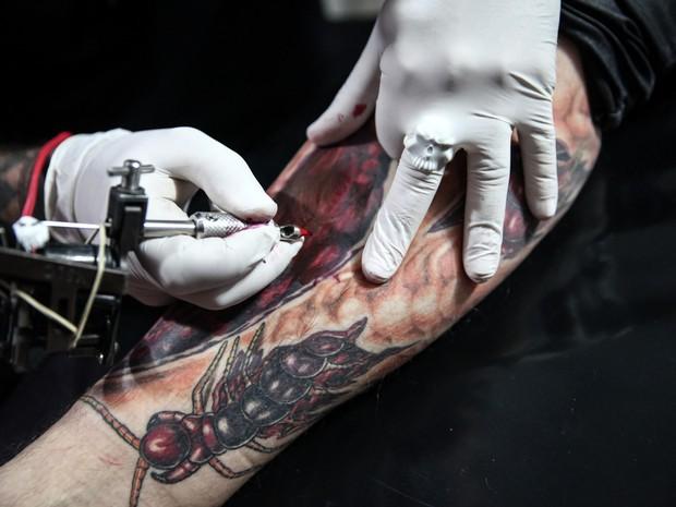 O tatuador Jhon Tattoo, responsável por todas as tatuagens visíveis no corpo do Coveiro Maldito, agora trabalha no desenho de uma fratura exposta na canela do amigo (Foto: Fábio Tito/G1)