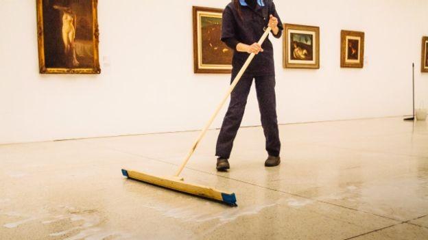 Funcionária do museu Oscar Niemeyer faz a limpeza da sala de exposições que exibiu obras apreendidas na operação Lava Jato (Foto: Marcio Pimenta Foto Series)