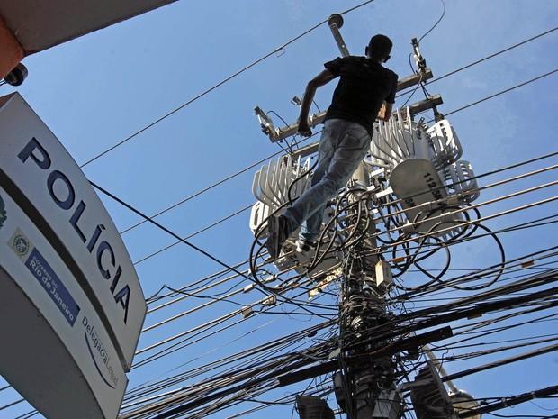 Homem cai eletrocutado depois de subir em poste em frente a 17º DP, São Cristóvão, na Zona Norte do Rio de Janeiro. Ele morreu devido à descarga elétrica (Foto: João Laet/Agência O Dia/Estadão Conteúdo)