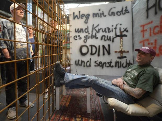 Ser humano em gaiola faz parte de exposição alemã (Foto: Reuters)
