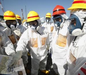 O primeiro-ministro do Japão, Shinzo Abe (de capacete vermelho), visita a Usina Nuclear de Fukushima Daiichi, no Nordeste do país. O governo vai investir o equivalente a R$ 1,1 bi para conter vazamento de água radioativa (Foto: AP Photo/Japan Pool)