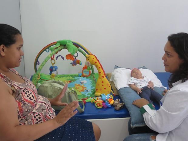 Fisioterapeuta Vanessa orienta a mãe Jaqueline (Foto: Mariane Rossi/G1)