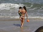 Daniele Suzuki exibe boa forma em dia de praia com o filho e o pai