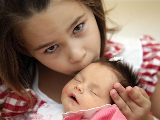 Maria Vitória beija a irmã recém-nascida Maria Clara, que foi selecionada geneticamente para poder ajudar a irmã (Foto: Evelson de Freitas/AE)