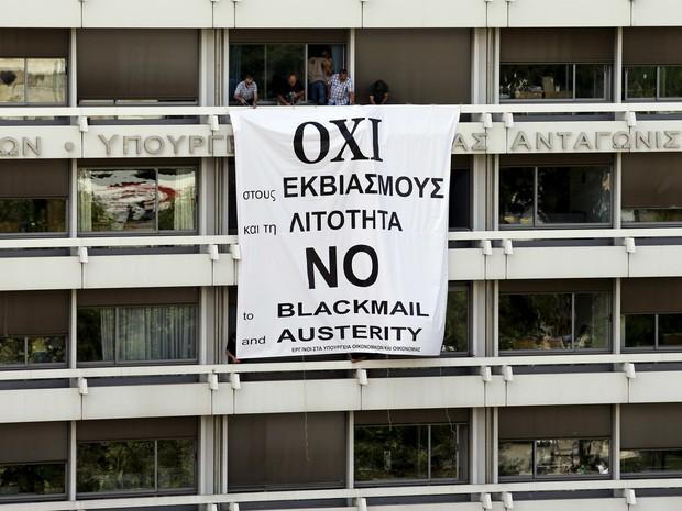Funcionários do Ministério das Finanças e da Economia Nacional da Grécia colocam uma bandeira na varanda do Ministério em Atenas com a mensagem 'Não à chantagem e à austeridade'. O país não pagou uma parcela da dívida de € 1,6 bilhão com o FMI (Foto: Jean-Paul Pelissier/Reuters)