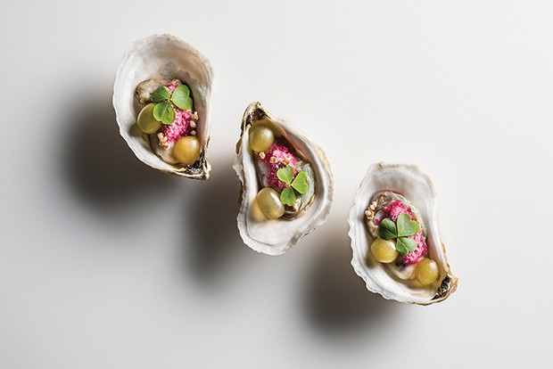Three Widow's Hole Oyster with baby green grapes topped with lucky sorrel, crispy bulgur wheat, and a dusting of grape mignonette snow on a white background.  Prepared by Daniel Humm, Chef/Owner of Eleven Madison Park, NY. (Foto: Photography: © 2013 Francesco T)