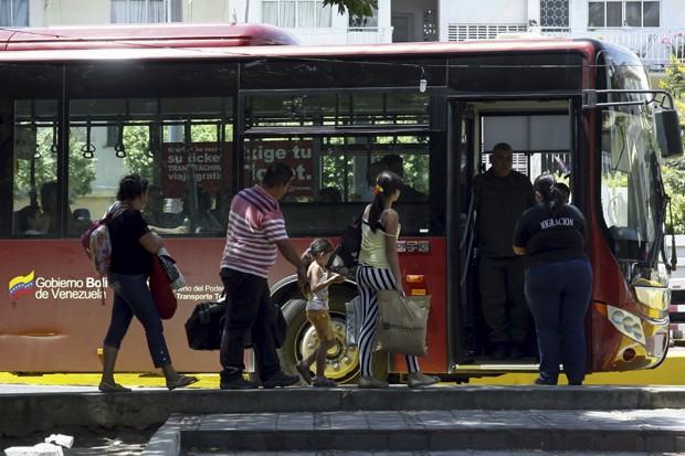 Pessoas caminham ao lado de oficiais de fronteira a bordo de um ônibus do governo para atravessar para a Colômbia, em San Antonio, no estado Táchira (na Venezuela) (Foto: Carlos Eduardo Ramirez/ Reuters)