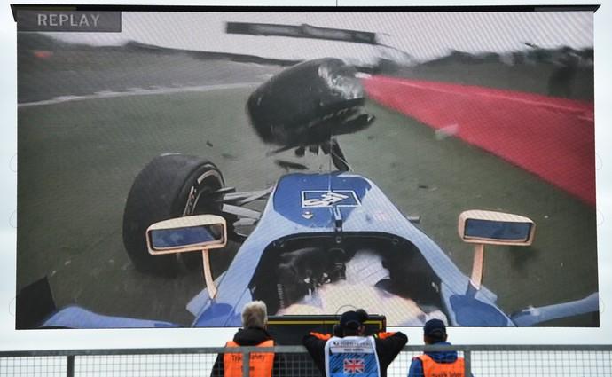 Fiscais observam em telão batida de Marcus Ericsson no 3º treino livre para o GP da Inglaterra (Foto: AFP)