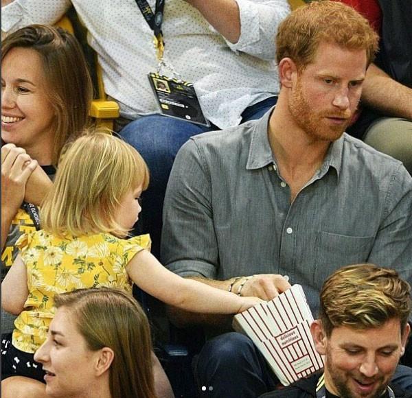 emily bem à vontade pegando a pipoca do Príncipe Harry (Foto: Reprodução - Instagram)