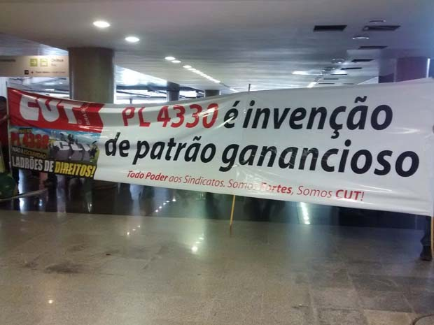 Integrantes da CUT seguram cartaz contra projeto de lei em frente a área de desembarque no aeroporto (Foto: Isabella Calzolari/G1)