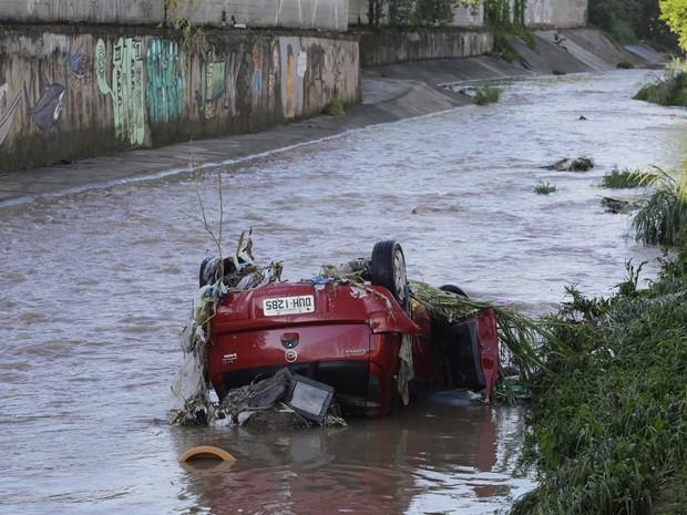 Carro é visto revirado dentro do córrego Pirajuçara, na região do bairro do Campo Limpo, divisa com Taboão da Serra, após ser arrastado pela forte chuva que atingiu São Paulo na noite de quarta-feira (22). (Foto: Nelson Antoine/Fotoarena/Estadão Conteúdo)
