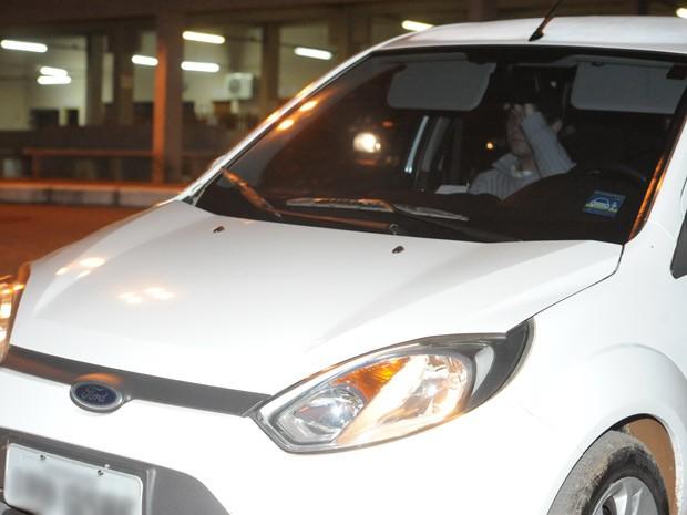 Acusado esconde o rosto ao deixar a penitenciária (Foto: Fernando Ramos/Agência RBS)