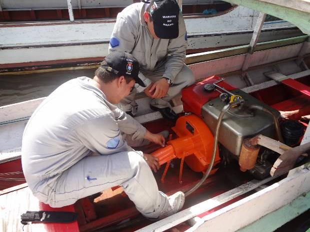 Equipe da Capitania dos Portos colocando a proteção de metal no motor de um barco na Feira do Açaí, no complexo do Ver-o-peso, em Belém (Foto: Natália Mello/G1)