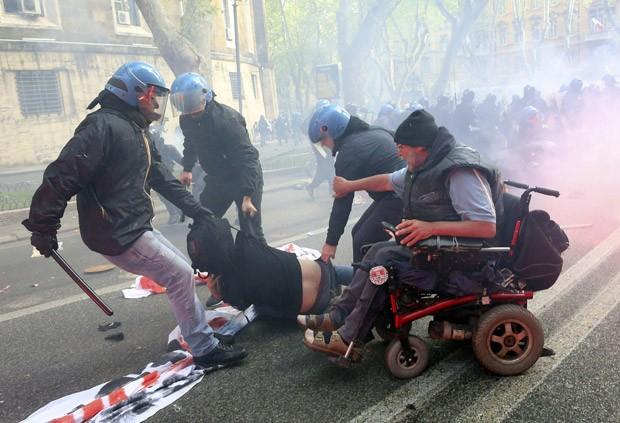 Manifestante caído é levado detido por policiais em meio ao confronto (Foto: Alessandro Bianchi/Reuters)