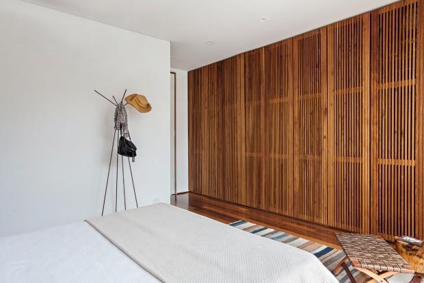 A porta de Formica fica em batente de madeira que tem a altura do pé-direito. O forro da Gesso Porto Seguro esconde a cobertura metálica da Calhas Plaza (Foto: Alessandro Guimarães / Divulgação)