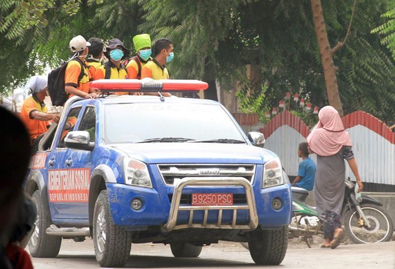 Homens que auxiliam no resgate usam máscaras por causa do vulcão Sangiang, que entrou várias vezes em erupção desde sexta-feira (30) na Indonésia. Voos foram cancelados