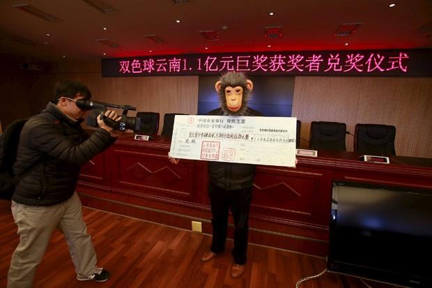 Ganhador de loteria usou máscara ao receber prêmio milionário na China (Foto: Reuters)