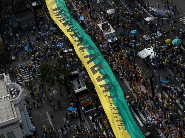 SÃO PAULO - Manifestantes estendem faixa verde e amarela com os dizeres 'Intervenção Já!' durante protesto contra a presidente Dilma Rousseff na Avenida Paulista (Foto: Miguel Schincariol/AFP)