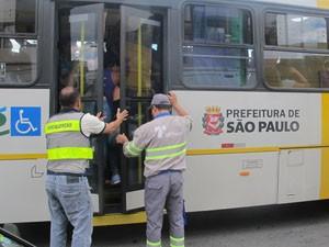 Funcionários da SPTrans tentam fechar porta de ônibus lotado (Foto: Roney Domingos/G1)