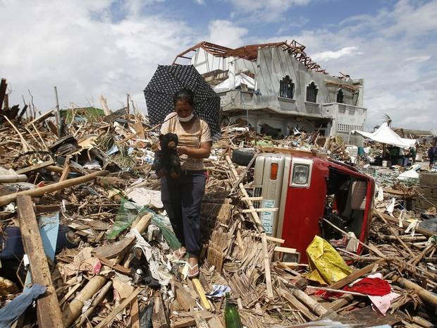14/11 - Mulher recupera um ursinho de pelúcia dentre os destroços de casas derrubadas na passagem do tufão Haiyan em Tanauan, na ilha de Leyte (Foto: Erik de Castro/Reuters)