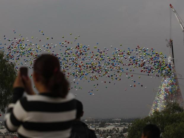 """Uma mulher retrata a imagem de cerca de 120 mil balões sendo lançado para o céu durante o """"Natal na sua vontade"""". Pessoas foram incentivadas a escrever seus desejos de Natal sobre os balões, que então tinham sido depositados em uma árvore de Natal de 34 m (Foto: REUTERS / Bernardo Montoya )"""