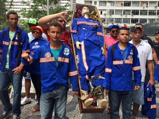 Funcionários do Comperj levaram um caixão com um boneco uniformizado ao protesto (Foto: Cristina Boeckel / G1)