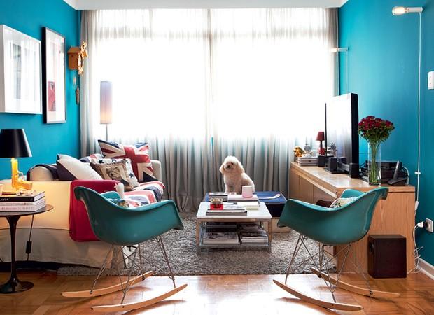 Entre os móveis da sala em tons de azul reina o cão Francisco. A cortina de linho cru, da NP Decorações, quebra a entrada de luz. Nas paredes, o turquesa escuro é da tinta R327, da Suvinil. Cadeiras de balanço Charles Eames, da Desmobilia. Luminárias da R (Foto: Lufe Gomes)
