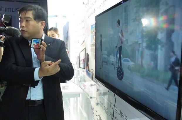 Lee Sung Jin, gerente sênior da divisão de plataformas da LG Electronics Mobile Communications mostra transmissão simultânea de conteúdos diferentes no smartphone e na tela da TV. (Foto: Daniela Braun/G1)