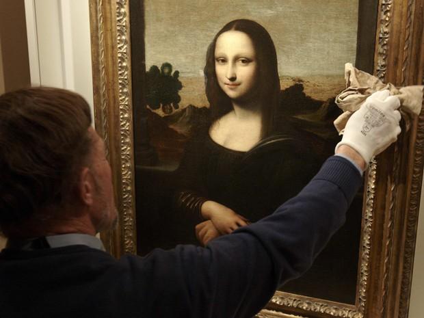 David Feldman, vice-presidente da Fundação Mona Lisa, limpa o vidro sobre a pintura que atribui a Leonardo da Vinci (Foto: Reuters/Denis Balibouse)