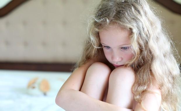 Criança triste com dor nas pernas (Foto: Shutterstock) .