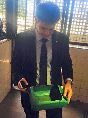 Deputado mostra recipiente de produto de limpeza usado como bebedouro e comedouro de animais no DF (Foto: Ricardo Izar/Divulgação)