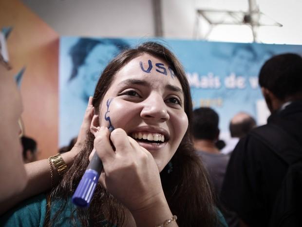 Aluna aprovada na USP tem o rosto pintado durante divulgação do resultado da primeira chamada da Fuvest (Foto: Caio Kenji/G1)