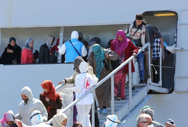 Imigrantes resgatados de barcos pela Itália chegam à Sicília nesta quarta-feira (22) (Foto: Francesco Malavolta/AP)