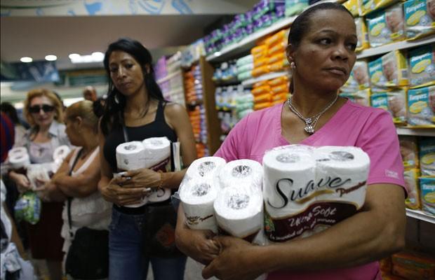 Mulheres seguram rolos de papel higiênico em fila de supermercado de Caracas, nesta sexta-feira (17) (Foto: Jorge Silva/Reuters)