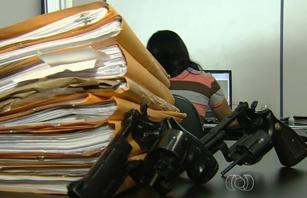 Arquivos de homicídios e armas apreendidas com suspeitos, em Goiânia (Foto: Reprodução/TV Anhanguera)