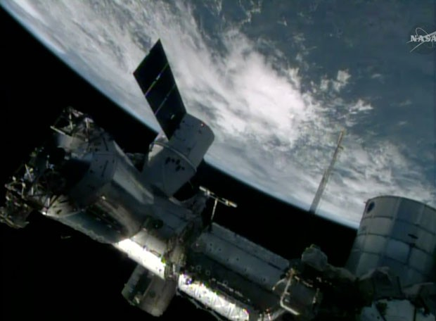 Imagem da Nasa TV mostra a cápsula de abastecimento Dragon acoplada à Estação Espacial Internacional neste domingo (20) (Foto: NASA-TV/AP)