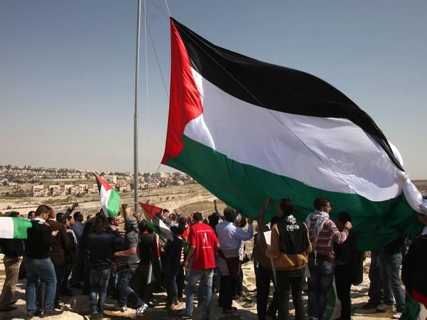 Palestinos levantam bandeira próximo ao maior assentamento judaico no subúrbio de Jerusalém, onde passará nesta quarta-feira (20) o presidente americano, Barack Obama (Foto: Abbas Momani/AFP)