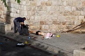 Policial recolhe pertences de agressor morto a tiros no Portão dos Leões, em Jerusalém (Foto: Mahmoud Illean/AP)