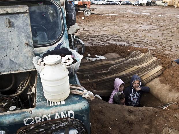 Crianças aguardam dentro de trincheira cavada por familiares ao lado de um caminhão sob risco de ataque de morteiros pelo Estado Islâmico em Kobani, Síria. Dos 50 mil moradores, apenas 2 mil civis seguem no local lutando e esperando o fim do conflito (Foto: Jake Simkin/AP)