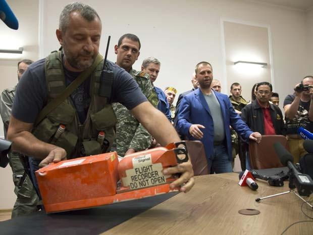 Combatente pró-Rússia apresenta caixa-preta do voo MH17 nesta segunda-feira (21) na cidade de Donestk (Foto: AP Photo/Dmitry Lovetsky)