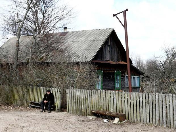 Ivan Shamyanok senta em frente à sua casa, perto da usina nuclear de Chernobyl, na Ucrânia (Foto: REUTERS/Vasily Fedosenko)