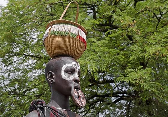 Mulher mursi com pintura fácil e botoque carrega cesto na cabeça (Foto: © Haroldo Castro/ÉPOCA)